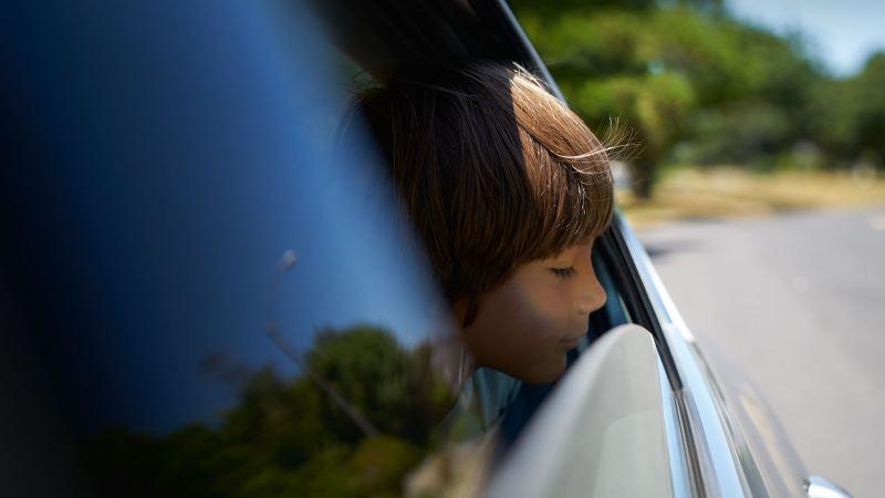 Pojke tittar ut från bilfönster