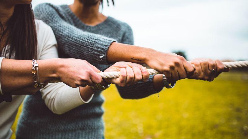 Primer plano de manos tirando juntas de una cuerda delante de un prado