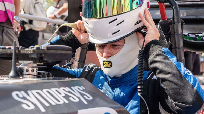 Fahrer Lukas setzt sich den Fahrerhelm auf