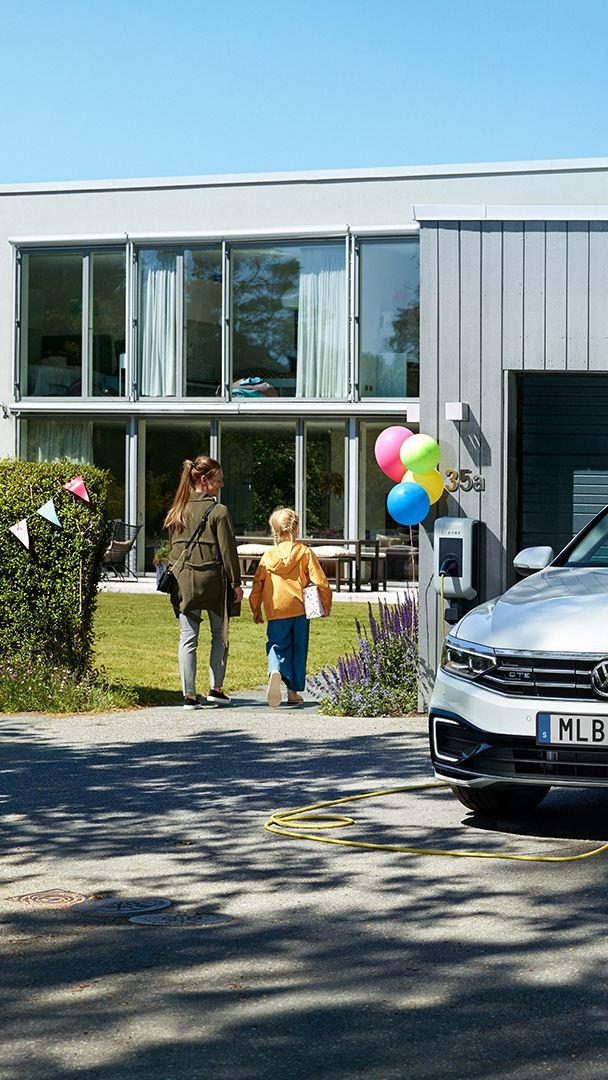 VW Passat GTE Sportscombi står på laddning framför ett garage som är utsmyckat med ballonger