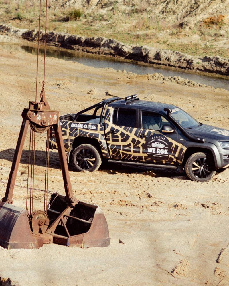 Ein Volkswagen Amarok steht in einer Kiesgrube mit einem Kranbagger im Vordergrund.