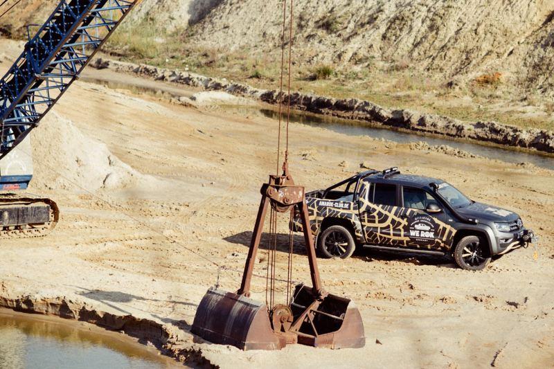 Ein VW Amarok steht in einer Kiesgrube mit einem Kranbagger im Vordergrund.