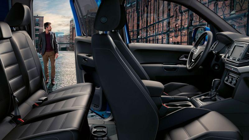 O interior do Volkswagen Amarok Aventura. Através da porta aberta vê-se um homem a caminhar nas ruas da cidade.
