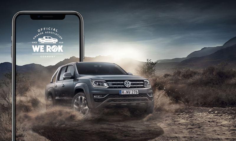 Der Amarok fährt dynamisch aus einem überdimensionalen Smartphone heraus in eine staubige Steppenlandschaft.
