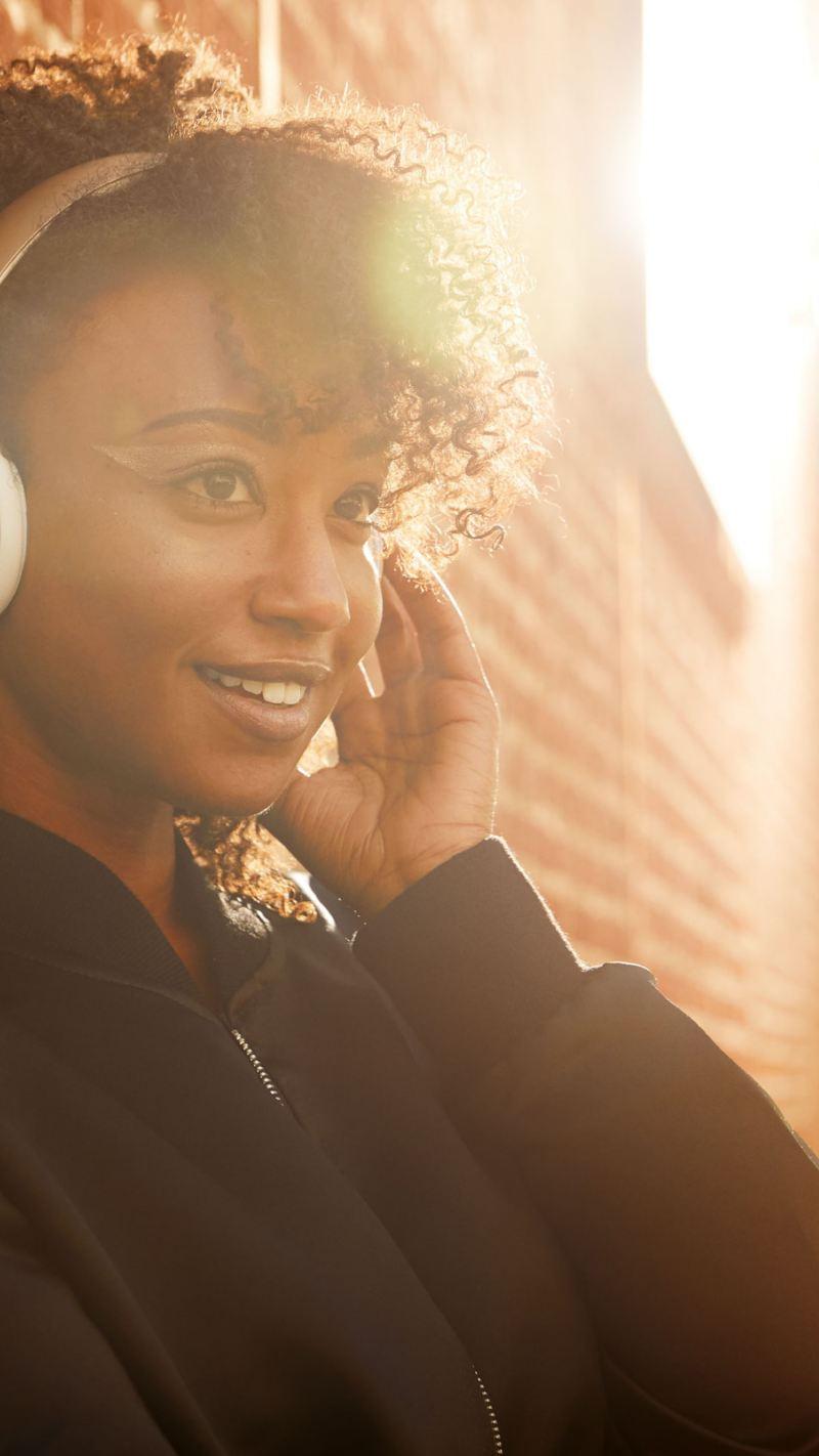 Junge Fahrer Versicherung - Frau lehnt an Wand und hört Musik