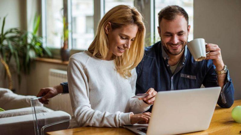 Eine Frau und ein Mann schauen auf einen Laptop.