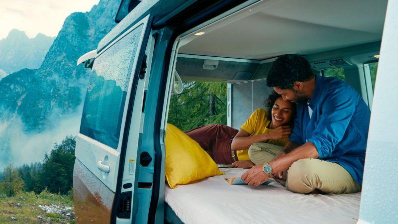 Um casal está deitado na cama da autocaravana Volkswagen California 6.1 Ocean a relaxar.