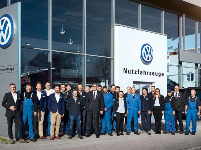 Mitarbeiter von Volkswagen Nutzfahrzeuge stehen vor einem Autohaus.