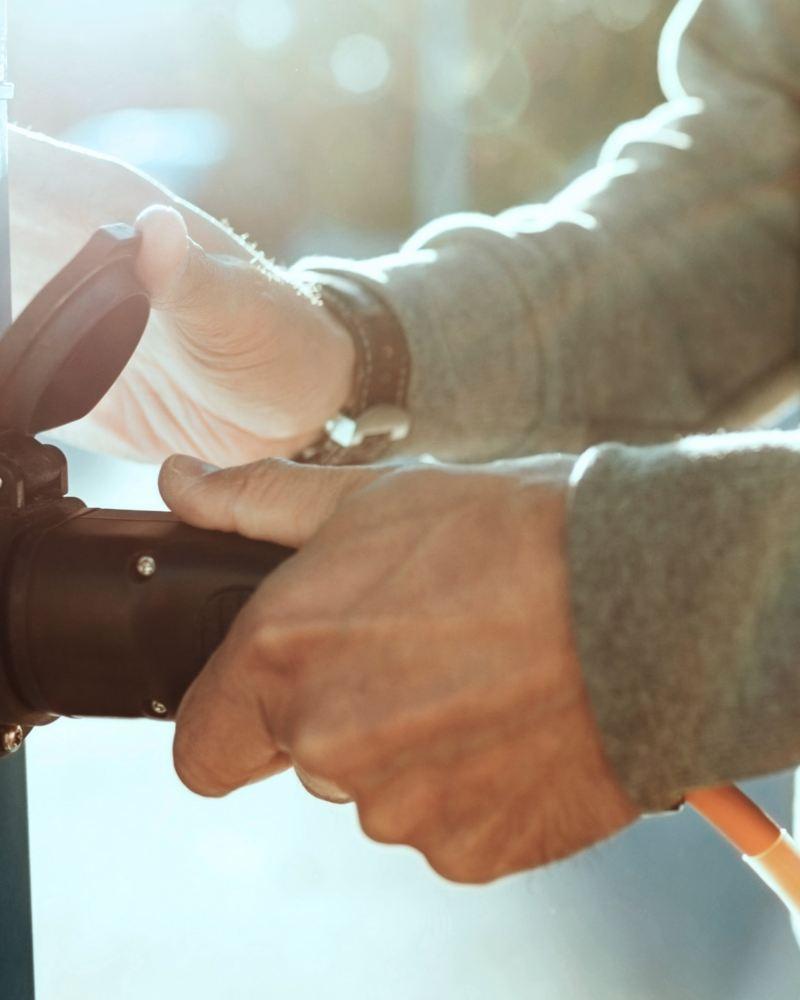 Zwei Hände stecken einen Stecker in eine Steckdose.