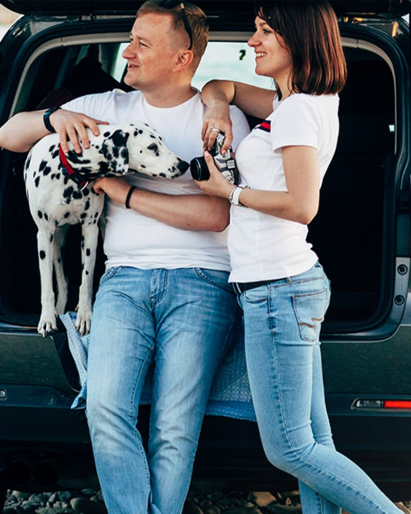 Pareja con mascota utilizando prendas y accesorios de la Colección Pets de Volkswagen