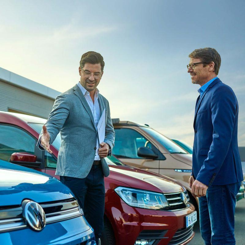 Ein Verkäufer zeigt einem Kunden ein Volkswagen Nutzfahrzeug.