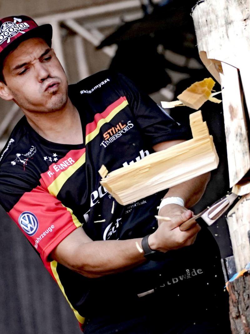 Ein Mann hackt mit einer Axt in einen präparierten Baumstamm.