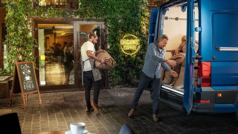 Kurier i barman rozpakowujący kawę z bagażnika e-Craftera