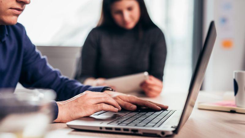 Ein Mann arbeitet am Laptop, eine Frau studiert ein Dokument