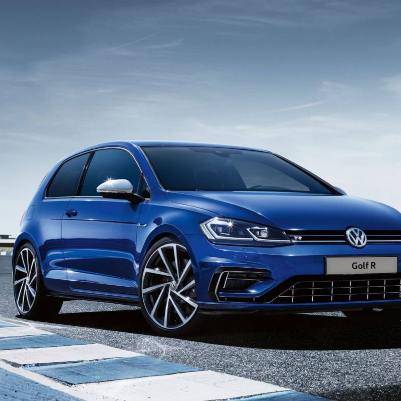 Rear view of a Volkswagen Golf R MK7 painted in Lapis Blue Metallic driving on a racetrack