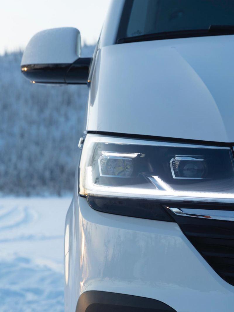 VW Multivan 6.1 minibuss i närbild i vinterlandskap