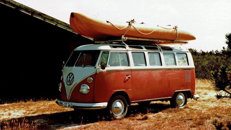 Ein Volkswagen T1 schräg von vorne mit Boot auf dem Dach.
