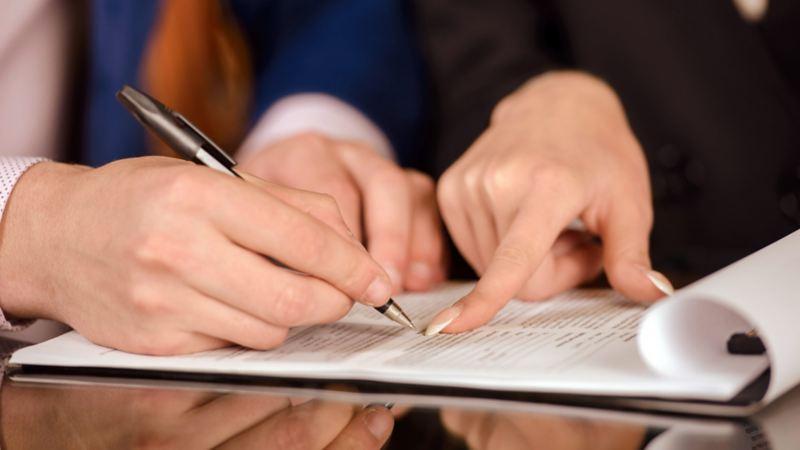 Mujer firmando contrato después de adquirir un auto usado Volkswagen