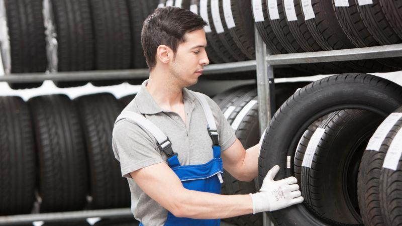 Ein Mechaniker nimmt einen Reifen aus einem Regal.