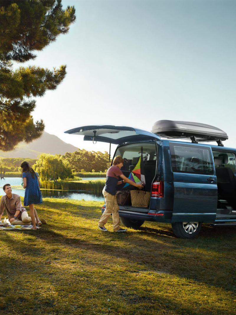 Människor på picknick med en VW transportbil i bakgrunden