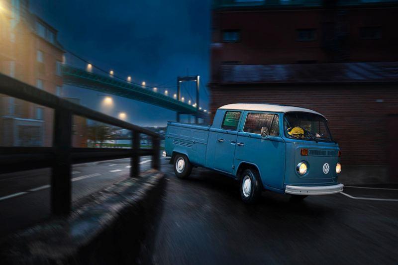 En duvblå VW pickup 1973 års modell i Göteborgs varv med Älvsborgsbron i bakgrunden