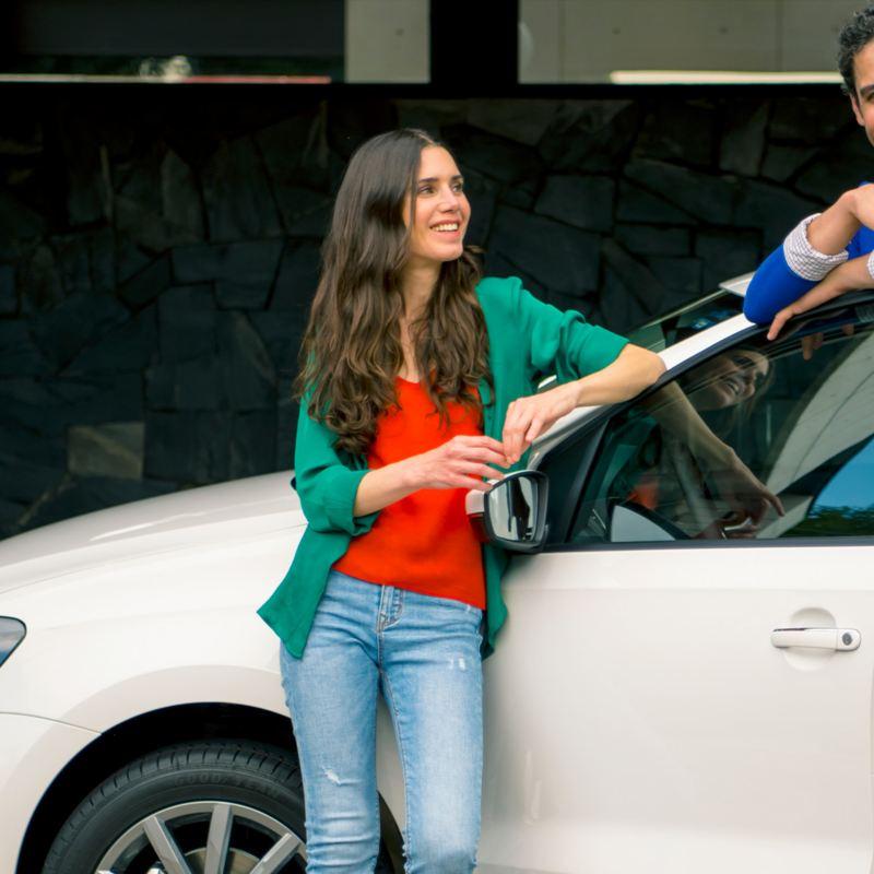 Pareja con auto adquirido con las mejores promociones de autos de Volkswagen