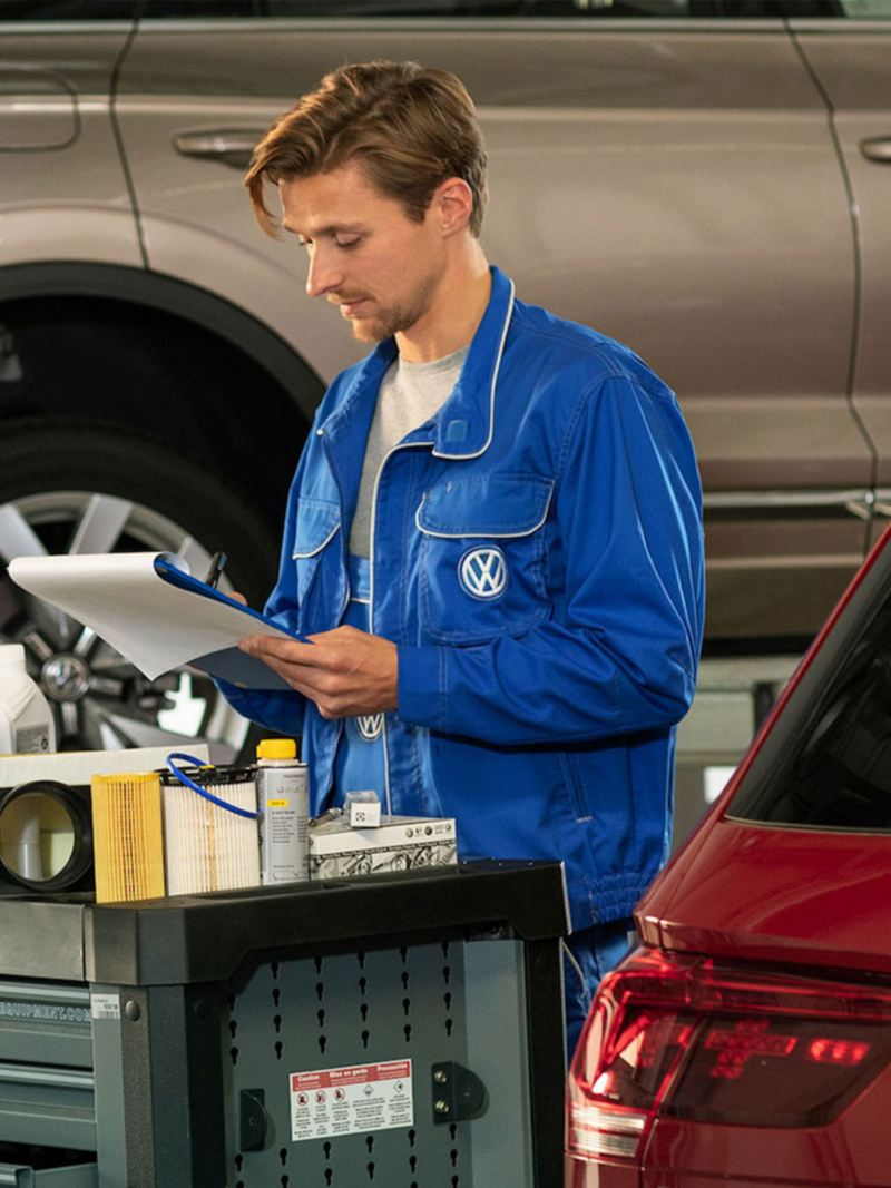 Técnico de Volkswagen realizando servicios de mantenimiento post-venta a automóvil