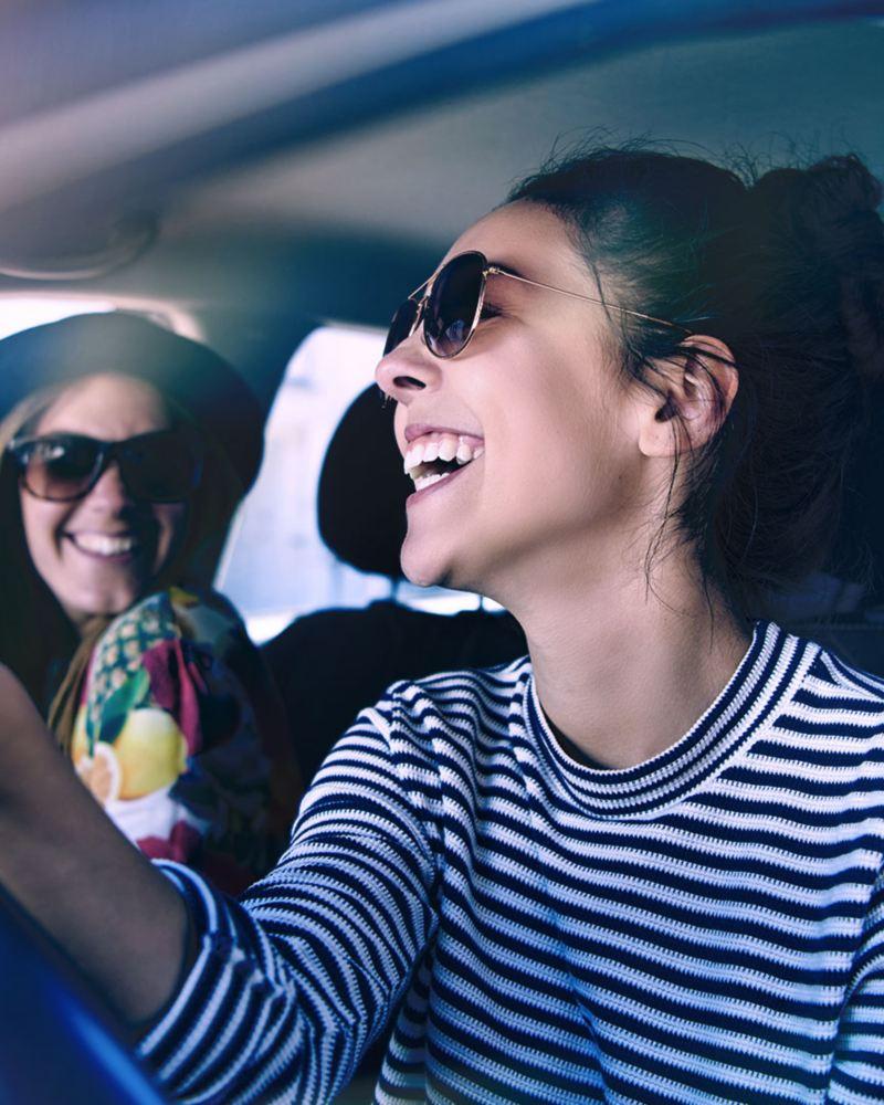 Amigas riendo dentro automóvil adquirido con crédito financiero Volkswagen para Personas con Servicios Financieros VW