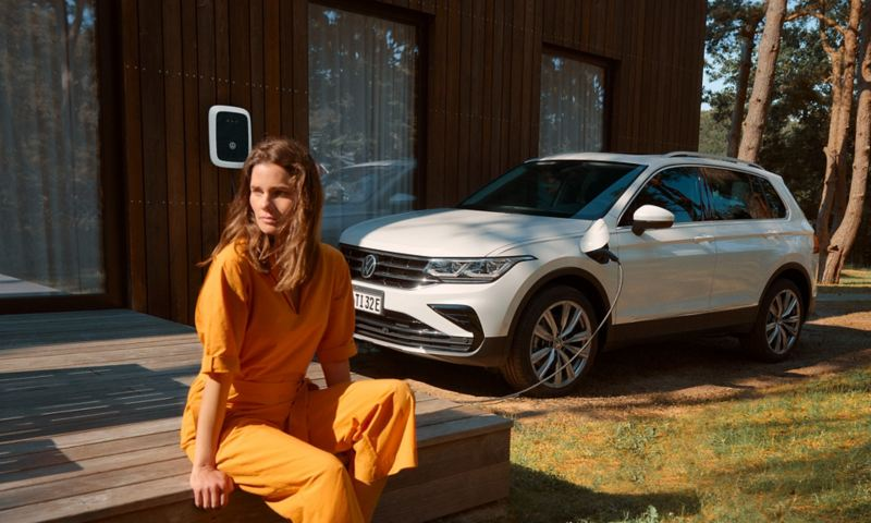 Una donna è seduta davanti a una VW Tiguan in carica presso una wallbox.