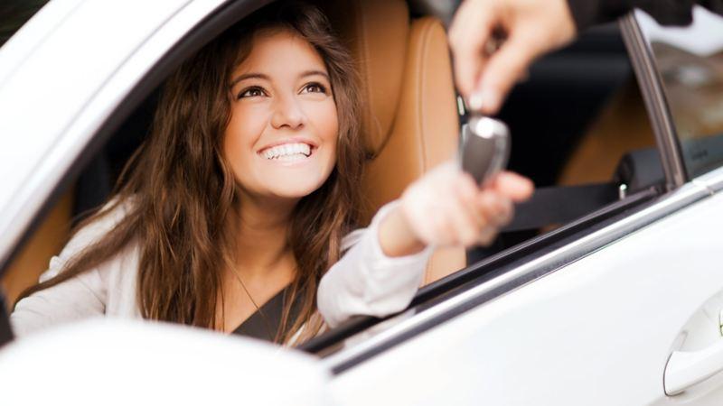 Mujer a bordo de su nuevo auto seminuevo Volkswagen con garantía incluida