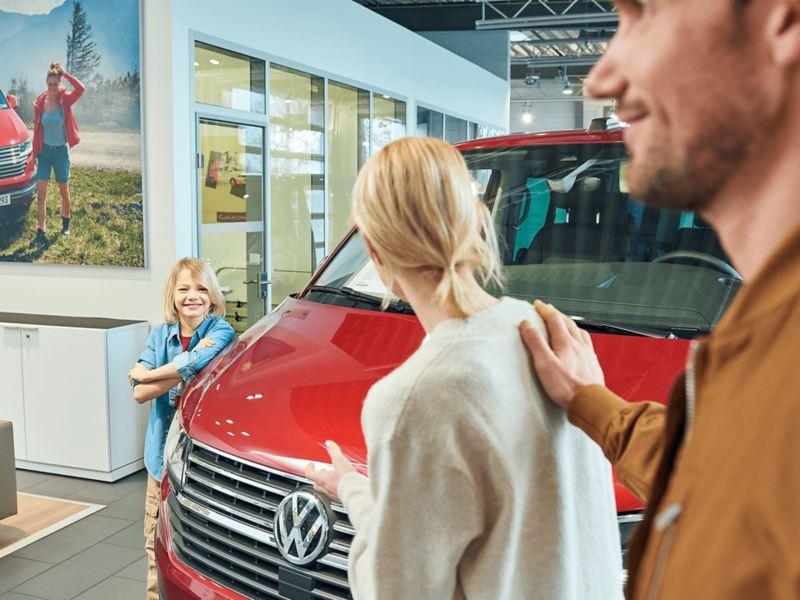 Eine Familie begutachtet einen von TradePort angebotenes Volkswagen Nutzfahrzeug.