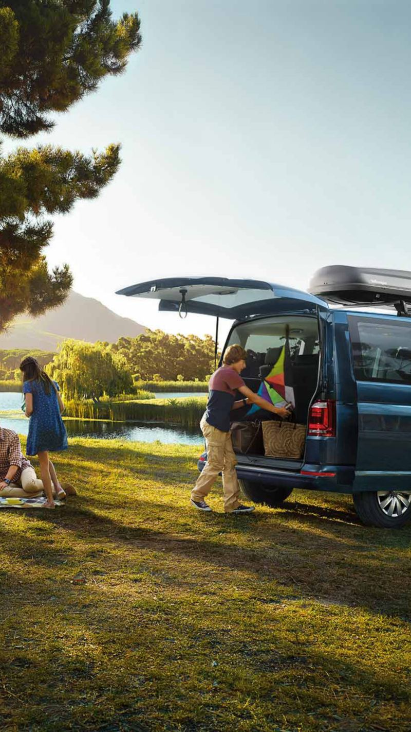 Familj ute på picknick med VW Caravelle