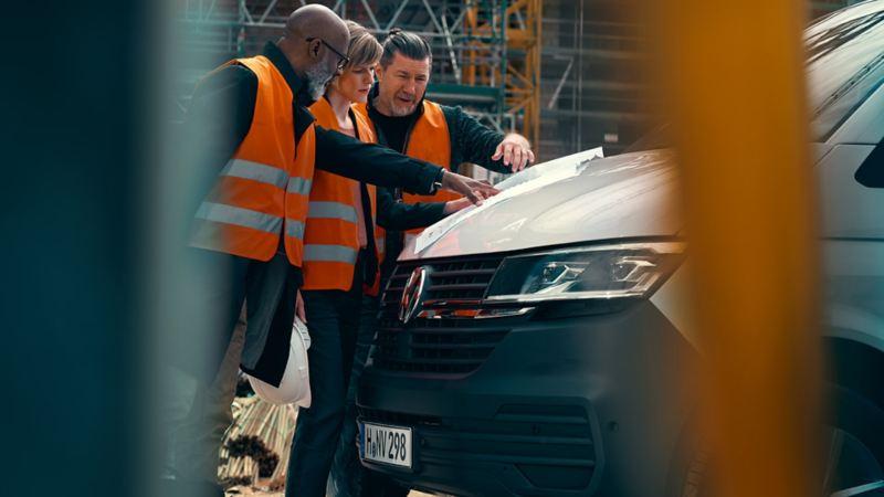 Två män och en kvinna diskuterar en ritning vid en VW Transporter Skåp