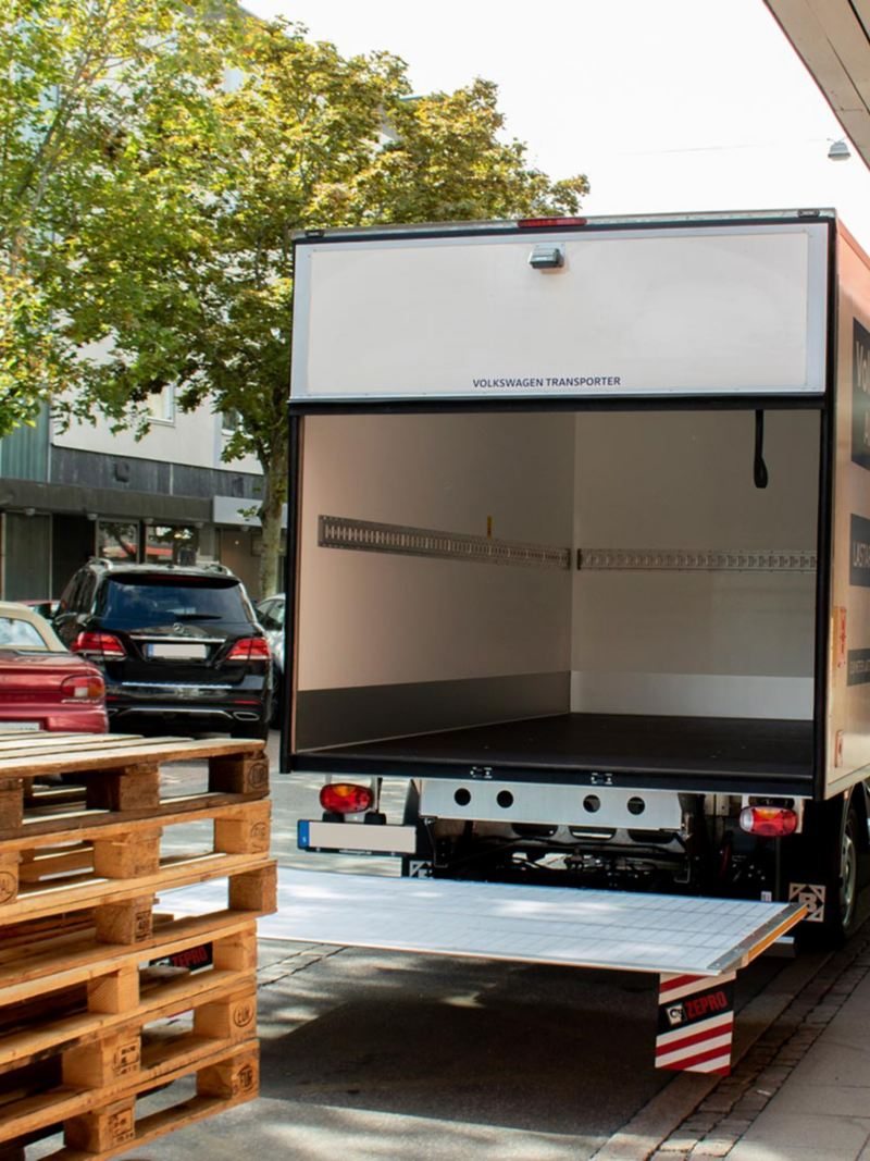 Vit VW Transporter VolyMax i en stad