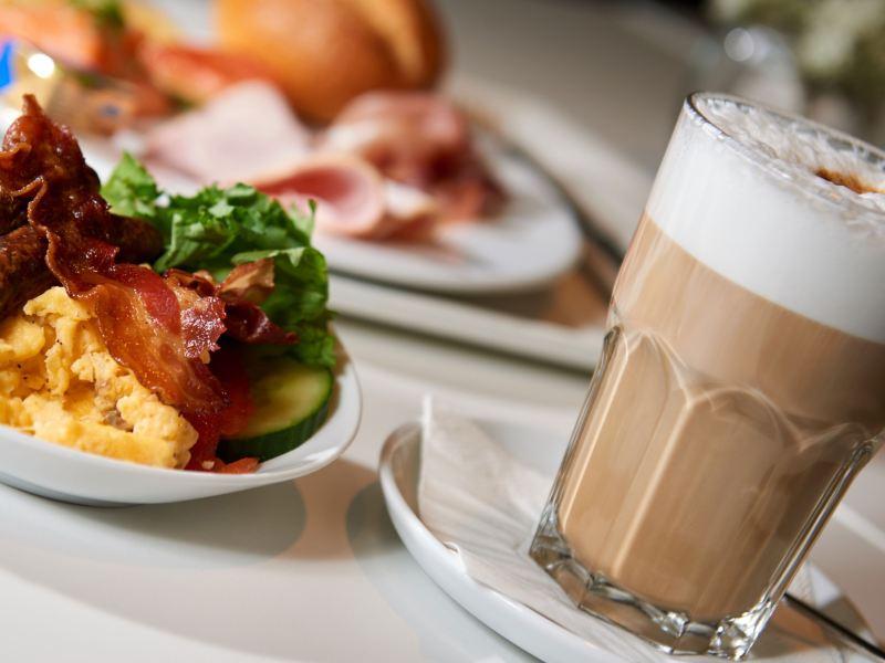Ein Milchkaffee und ein Rührei mit gebratenem Speck.