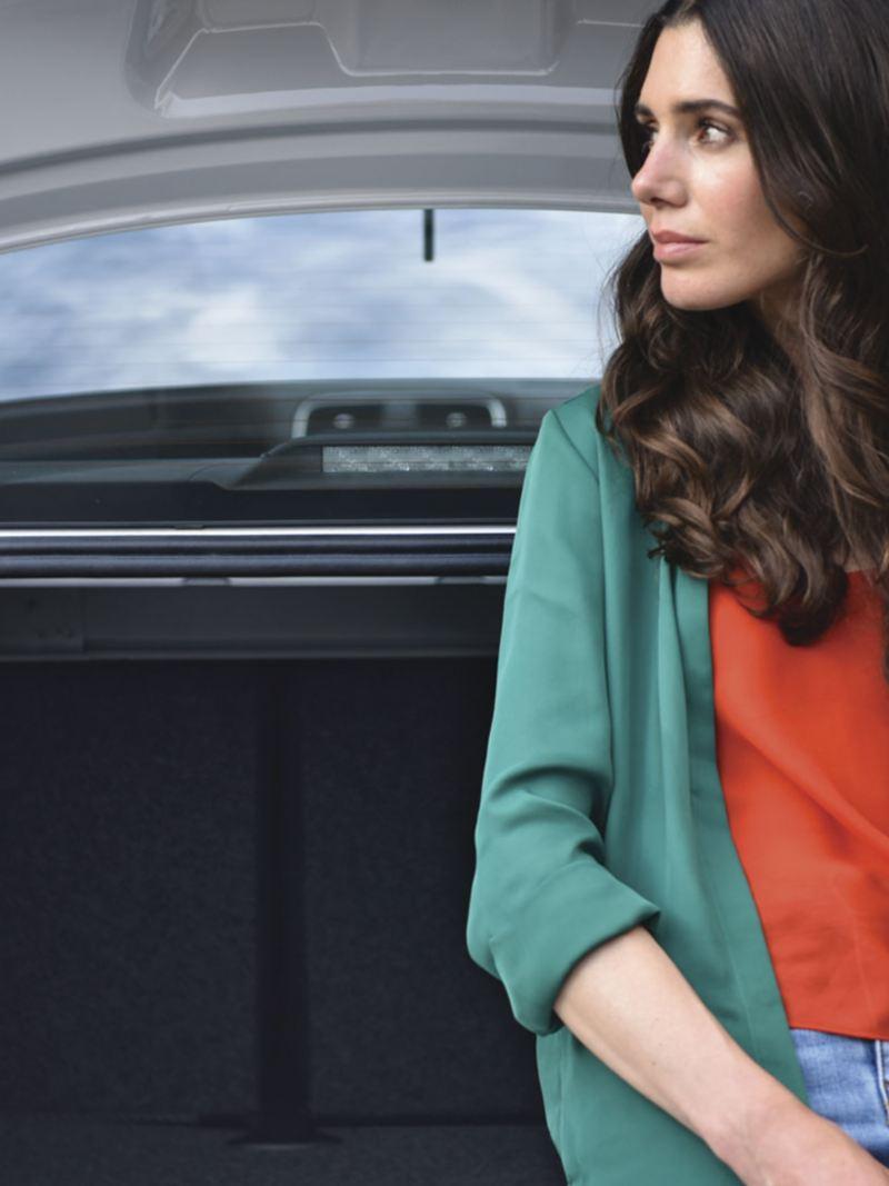 Mujer recargada en la cajuela del auto sedán Vento 2021 de Volkswagen