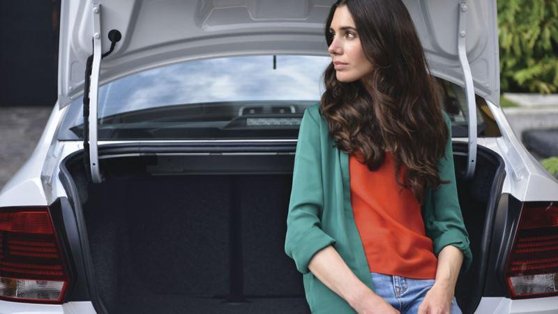Mujer recargada en la cajuela del auto sedán Vento 2020 de Volkswagen
