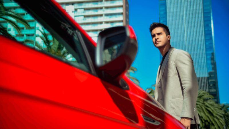 Hombre caminando ante Nuevo Virtus rojo tornado comprado a través de Leasing Volkswagen ¡Ya!