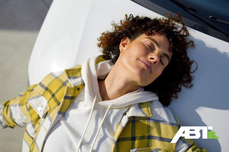 Une femme en train de profiter du soleil sur le capot du moteur de l'ABT e-Transporter 6.1.