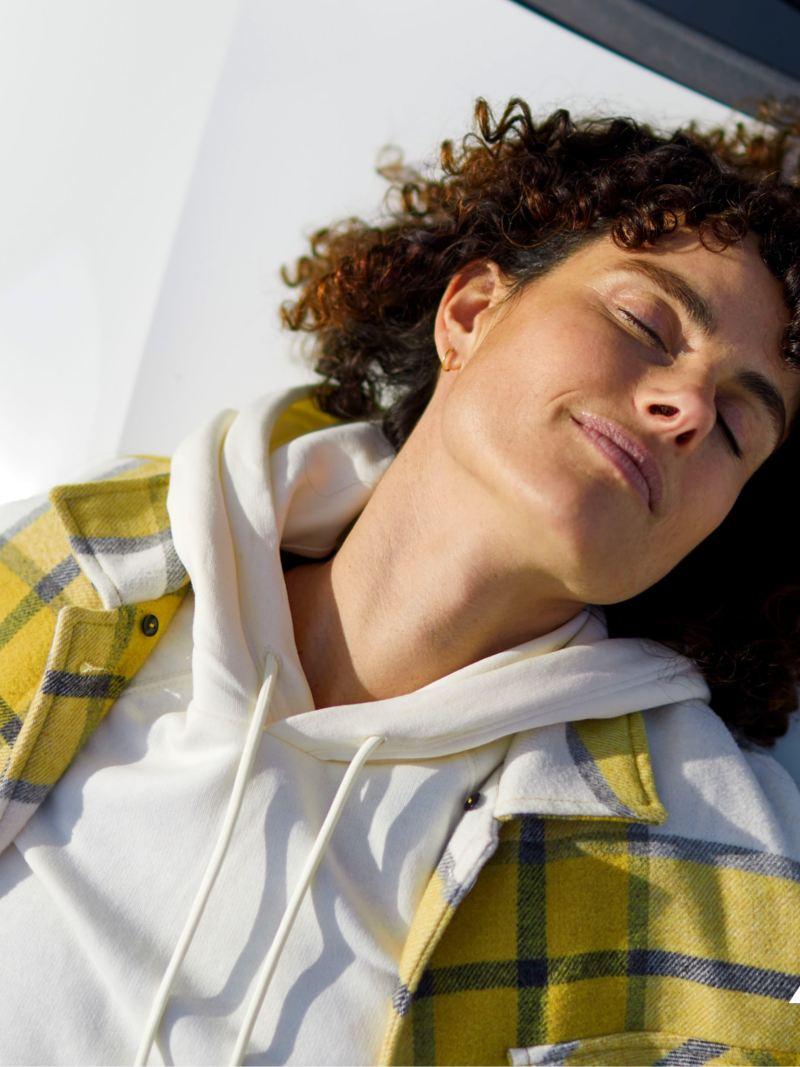 Una donna al sole appoggiata sul cofano dell'ABT e-Transporter 6.1.