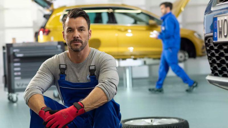 Ein VW Service Mitarbeiter sitzt auf einem Reifen