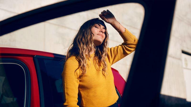 Eine Frau steht in der Sonne vor einem Volkswagen