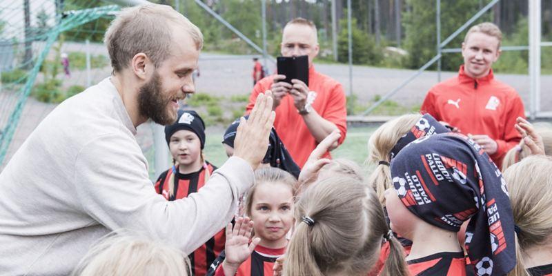 """Kuvassa jalkapalloilija Teemu Pukki antamassa """"yläviitosia"""" jalkapallojunioreille"""