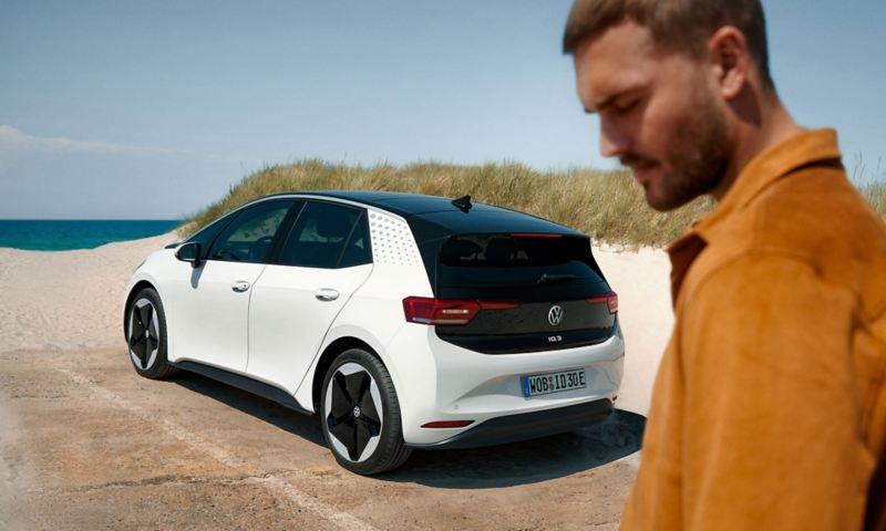 En mann på stranden med VW Volkswagen ID.3 i bakgrunnen.