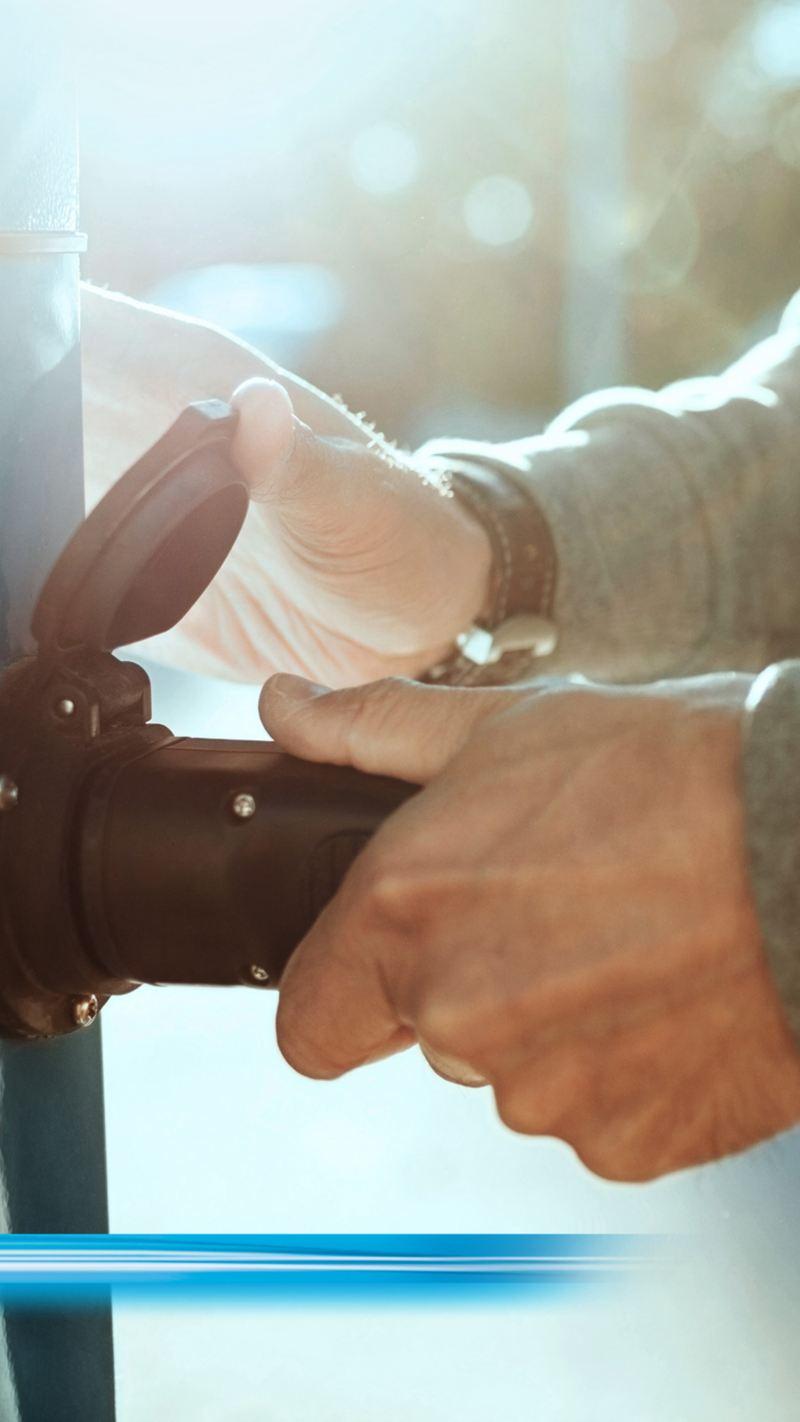 Deux mains branchent une fiche dans une prise de courant.