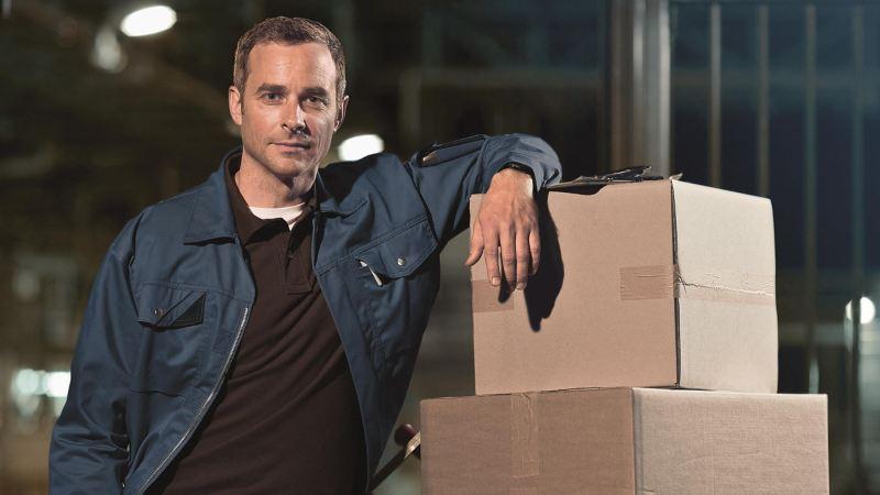 Mężczyzna opierający się o paczki.