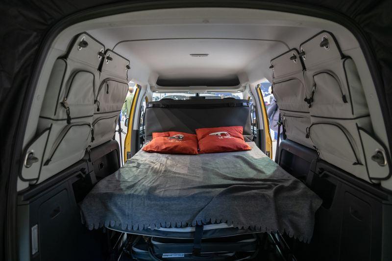 Wnętrze Caddy Beach z rozłożonym łóżkiem dla dwóch osób