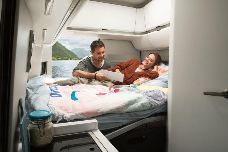 Mężczyzna i kobieta oglądają film leżąc na łóżku w Grand Californii, w tle otwarte drzwi z widokiem na jezioro i góry
