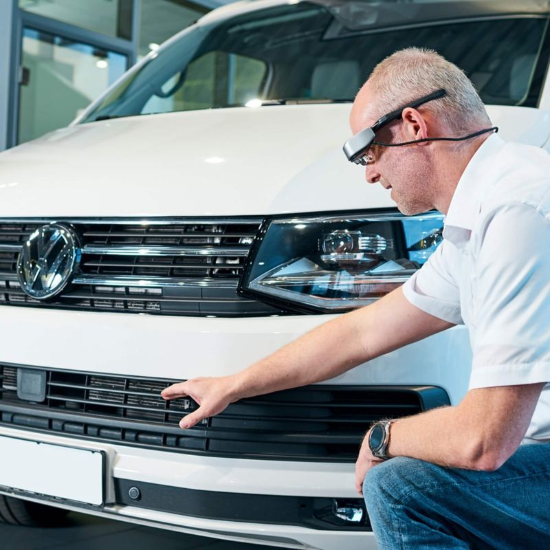 Ein Live Berater zeigt auf ein Detail am VW California.
