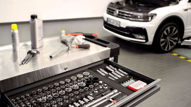 close up of tools and ratchet set with Volkswagen Golf in the background